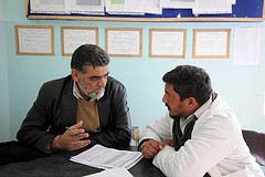 "Completing an inspection checklist sent out by the Afghan Basic Package of Health Services, Farah Hospital pharmacist Nasrullah Noori speaks with Dr. Fazil Ghani, the resident doctor at the clinic, during a clinic assessment, Dec. 29, 2009. The clinic employs 14 staff members, including civilian guards, one doctor, one nurse, one midwife, a pharmacist and other administrative officials, and is open 24 hours a day. ""There is always a doctor here,"" said Mohammad Sarwar, an administrative professional at the clinic who has been in charge of the clinic's logistics for the past three years. Noori travelled to the clinic in the Pusht Rod District of Farah Province, Afghanistan, with the Farah Provincial Health Director, Dr. Abdul Jabar, and other Farah Hospital medical providers; all of which were transported and accompanied by members of the Farah Provincial Reconstruction Team (PRT)."