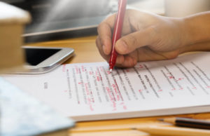 A hand holding a red pen and correcting a draft of source content to be translated